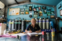 Crest Divers shop owner Sue Newson filling out her dive log - Jervis Bay © Danielle Ryan - Bluebottle Films Oct 2014
